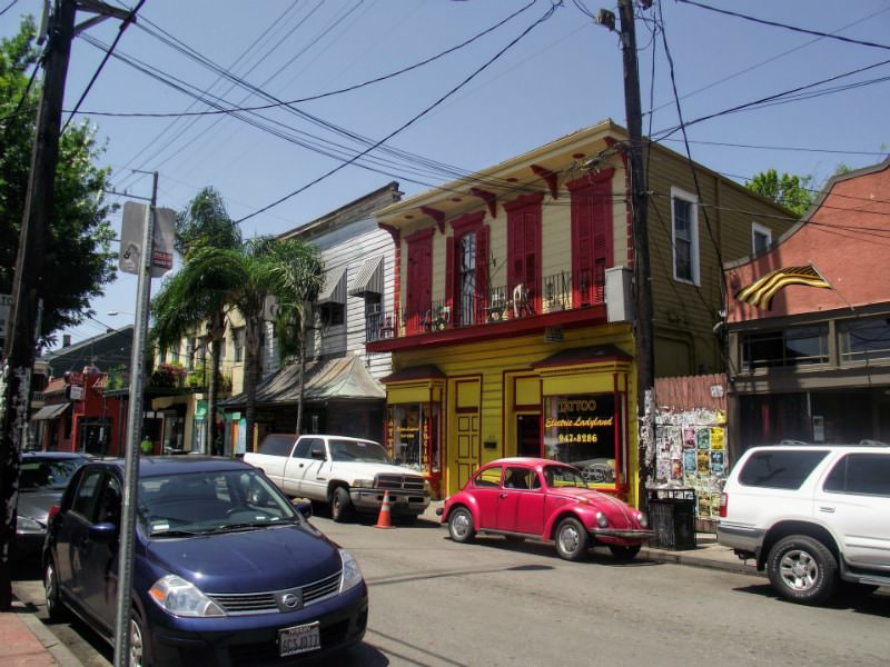 Cars are parked alongside buildings on Frenchman Street in New Orleans. This is an area where you can find several music venues.