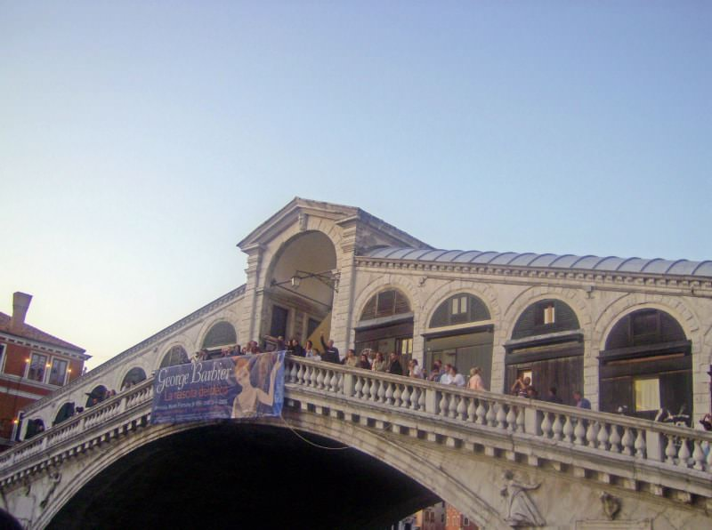People standing on the Rialto Bridge in Venice, Italy.